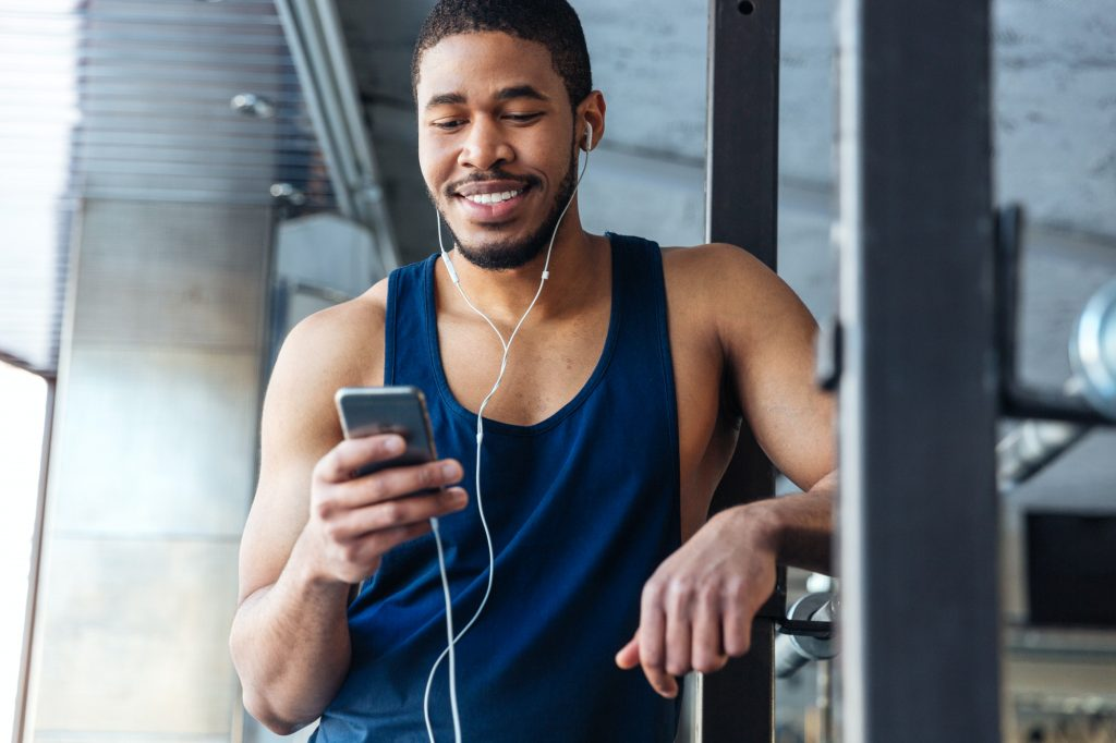 Smilling fitness man using smartphone in the gym